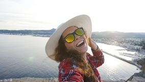 Happy woman traveler in sunglasses makes selfie with sea and mountain view. Happy woman traveler in sunglasses makes selfie with sea view stock video