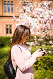 Happy woman traveler take photos by camera with cherry blossoms tree on vacation while spring royalty free stock images