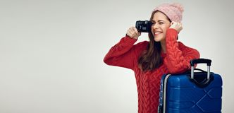 Happy woman traveler with travel case taking pictures with camer Stock Images