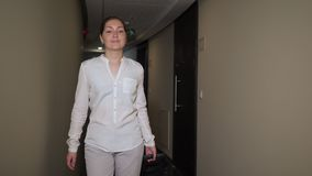 Happy woman traveler is walking on hotel corridor with suitcase. Happy young woman tourist is walking on hotel corridor with suitcase. She is looking for her stock footage