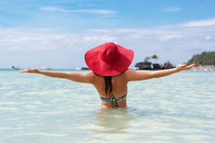 Happy woman in tropical paradise. Back view of fashion woman is swimming on the beach and wearing red hat, summer vacations Stock Photo