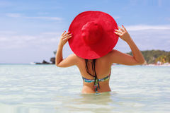 Happy woman in tropical paradise. Back view of woman is swimming on the beach and wearing red hat, summer vacations Royalty Free Stock Photos