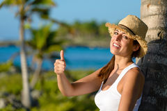 Happy woman on tropical vacation with thumbs up Royalty Free Stock Photo