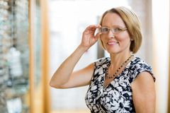 Happy Woman Trying On Eyeglasses In Store Stock Image