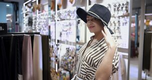 Happy woman trying on hat in clothing store, looking at camera and smiling, shopping