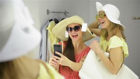 Happy Woman Trying a New Sunglasses in the Wardrobe at The Clothing Store. Female Friends Having Fun Shopping Clothes. Ladies Making Mirror Selfie in Fitting stock video