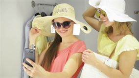 Happy Woman Trying a New Sunglasses in the Wardrobe at The Clothing Store. Female Friends Having Fun Shopping Clothes. Ladies Making Mirror Selfie in Fitting stock footage