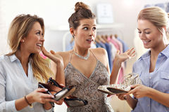 Happy woman trying to choose shoes. Picture of happy women trying to choose shoes in store Royalty Free Stock Images
