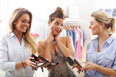 Happy woman trying to choose shoes. Picture of happy women trying to choose shoes in store Royalty Free Stock Photo