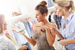 Happy woman trying to choose shoes. Picture of happy women trying to choose shoes in store Royalty Free Stock Photography