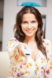 Happy woman with TV remote Stock Photography