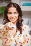 Happy woman with TV remote Royalty Free Stock Photos