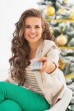 Happy woman with tv remote control in front of christmas tree Royalty Free Stock Image