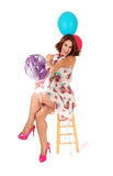 Happy woman with two balloons. A beautiful young woman siting on a chair, with legs crossed and holding Stock Images