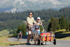 Happy woman and two boys are walking with luggage in mountain resort Royalty Free Stock Images