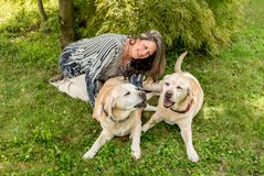 Happy woman with two labrador dogs. Happy woman with two labrador dogs on grass in the park Royalty Free Stock Photography