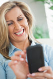 Happy woman typing on her mobile phone Stock Photos