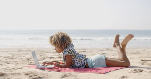 Happy Woman Typing On Laptop at Beach. Cute african-american woman typing on a laptop on a bench Royalty Free Stock Photos