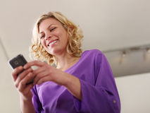 Happy woman typing text message on mobile phone. Young beautiful caucasian blonde woman typing e-mail message on smartphone and laughing. Low angle view, copy stock photo
