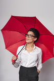 Happy woman with umbrella. Happy african american business woman standing with red umbrella, over gray background royalty free stock image