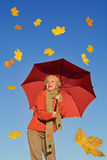 Happy woman with umbrella and falling leaves. Happy autumn woman with red umbrella under clear blue sky and falling leaves - warm afternoon light royalty free stock images