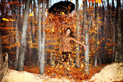 Happy woman with umbrella full of leafs and fun. Woman holding an umbrella full of leafs, and turning it to release all the leafs. Fun in autumn Stock Photo
