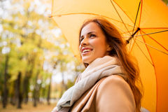 Happy woman with umbrella walking in autumn park Royalty Free Stock Image