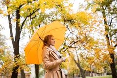 Happy woman with umbrella walking in autumn park Stock Photo