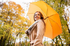 Happy woman with umbrella walking in autumn park Stock Images