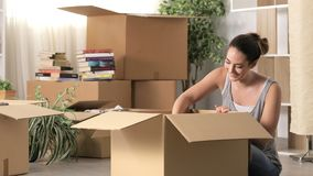 Happy woman unboxing belongings moving home stock video