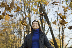 Happy Woman Under Falling Leaves In Park. Low angle view of a smiling young woman under falling leaves in park stock images