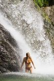 Happy woman under waterfall. Happy woman stay under cold water of a waterfall Stock Photography
