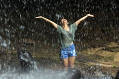 Happy woman under waterfall Stock Images