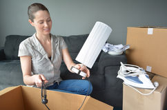 Happy woman unpack boxes during a move into a new home. Happy woman (age 30-35) unpack boxes during a move into a new home. Moving house concept. Real people Royalty Free Stock Images
