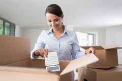 Happy woman unpacking Stock Images