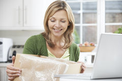 Happy Woman Unpacking Online Purchase At Home. Woman Unpacking Online Purchase At Home Stock Image