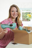 Happy Woman Unpacking Online Purchase At Home. Happy Woman Unpacks Online Purchase At Home Royalty Free Stock Photography