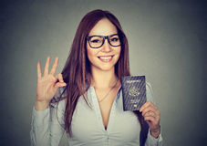 Happy woman with USA passport giving ok sign Stock Photos