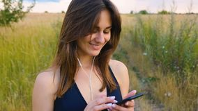 Happy young woman use smartphone and headphone standing in field at sunset, healthy lifestyle. Sportywoman runner using. Happy woman use smartphone and headphone stock footage