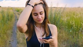 Happy young woman use smartphone and headphone standing in field at sunset, healthy lifestyle. Sportywoman runner using. Happy woman use smartphone and headphone stock video footage