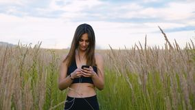 Happy young woman use smartphone and headphone walking in field at sunset, healthy lifestyle. Sportywoman runner using stock video footage