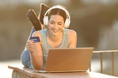 Happy woman uses credit card to buy online music or media royalty free stock photo