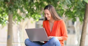 Happy woman uses a laptop on a bench in a park stock footage