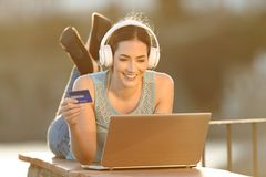 Happy woman uses a laptop to buy online music or media stock images