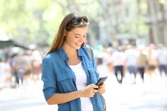 Woman uses a smart phone in the street. Happy woman uses a smart phone standing in the street Stock Photography