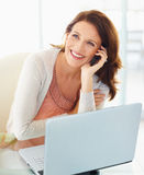 Happy woman using cellphone with laptop in front Royalty Free Stock Photography