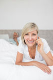 Happy woman using cellphone while man using laptop in bed Royalty Free Stock Photos