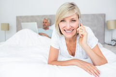 Happy woman using cellphone while man using laptop in bed Royalty Free Stock Photography