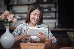 Happy woman using digital tablet in cafe stock image