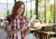 Happy woman using digital tablet in cafe royalty free stock photos